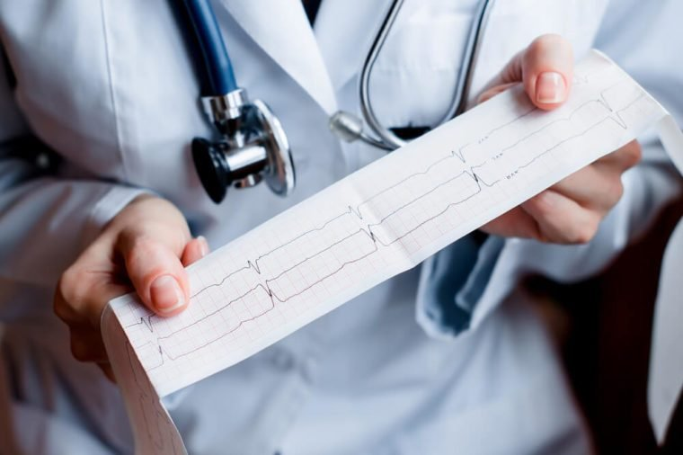 Electrocardiogram, ecg in hand, palm of a doctor. Medical health care. Clinic cardiology heart rhythm and pulse test closeup. Cardiogram printout.