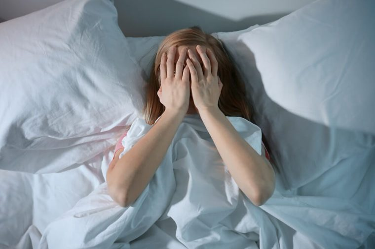 Young scared woman lying in bed at home