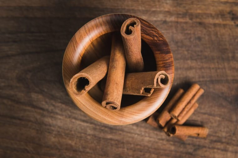 cinnamon in a wooden bowl of olive wood - Stock Image