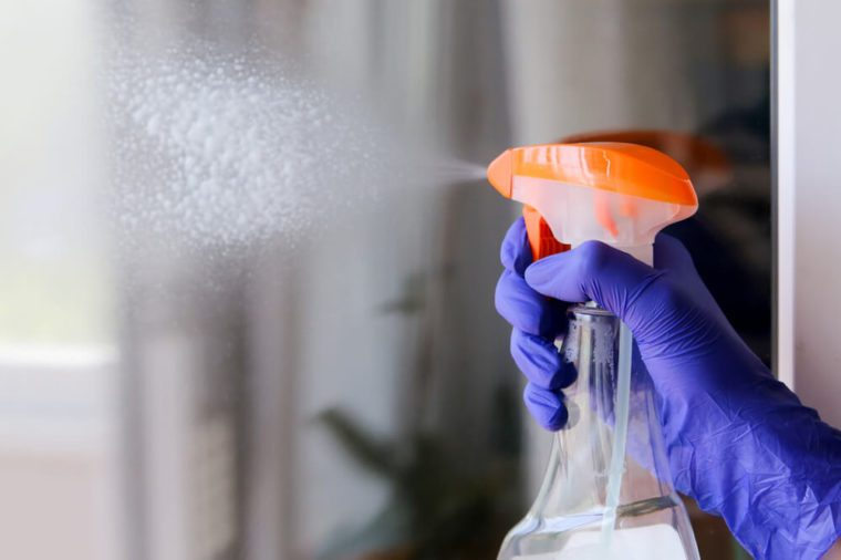 Woman cleaning a window with cleaning sprayer.