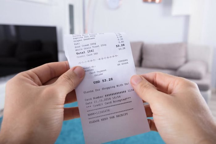 Close-up Of Person's Hand Holding Bill At Home