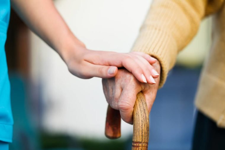 Doctor holding a senior patients 's hand on a walking stick - special medical care concept for Alzheimer 's syndrome.