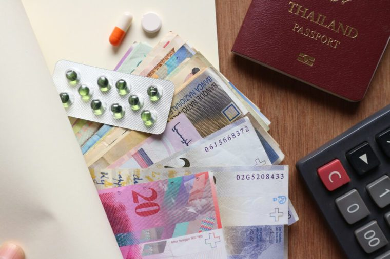 Various money with medicine panel, pill and capsule inside blank notebook with passport and calculator on wood table, finger on edge of book