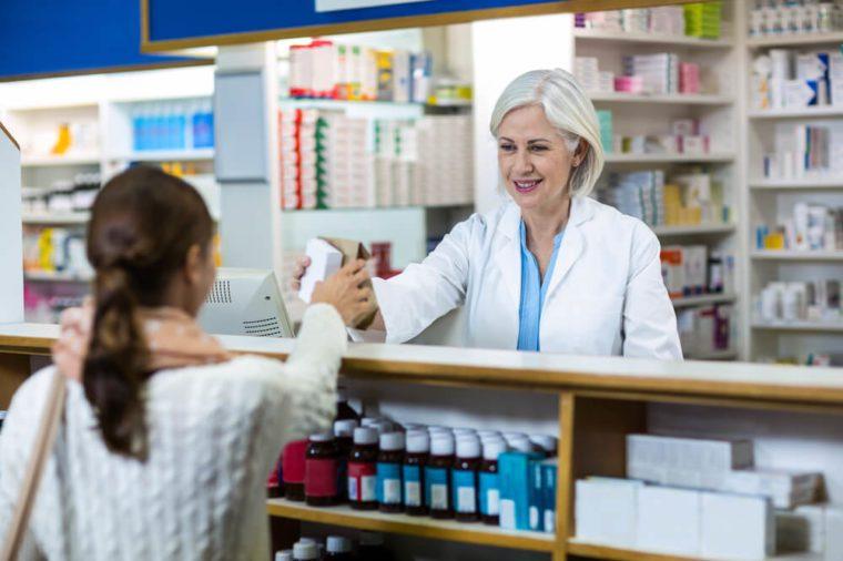 Pharmacist giving medicine box to customer in pharmacy