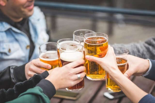 Group of friends enjoying a beer at pub in London, toasting and laughing. They are four girls and two boys in their twenties. Close up and focus on glasses.