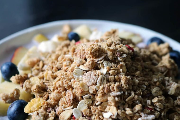 Close-up of a bowl of breakfast cereal with fruits and yogurt.