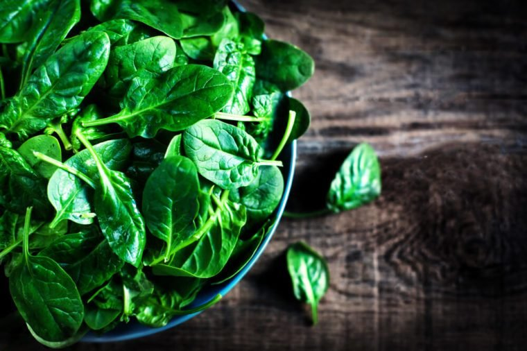 Fresh green baby spinach leaves in a bowl on a rustic wooden table close up