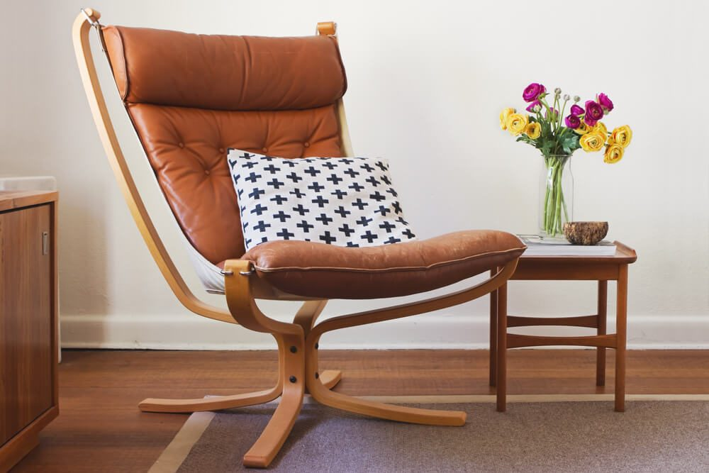 Retro tan leather chair and side table with flowers interior