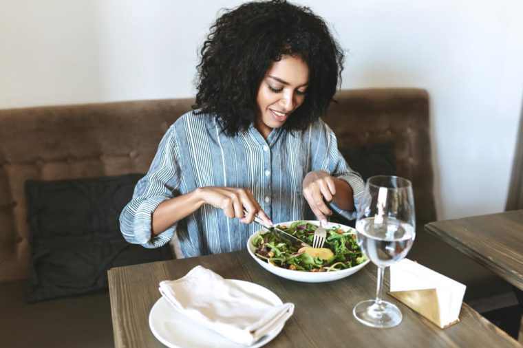 Young African American girl eating salad in restaurant. Beautiful girl with dark curly hair sitting at cafe and eating salad. Portrait of smiling lady that have lunch in restaurant