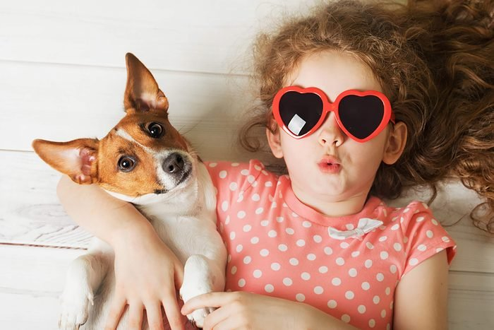 a girl in sunglasses lays on the floor with her cute puppy