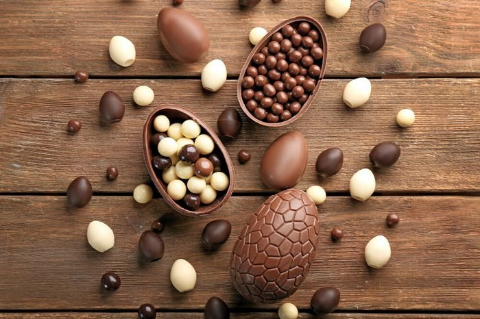 Chocolate Easter eggs and sweets on brown wooden background
