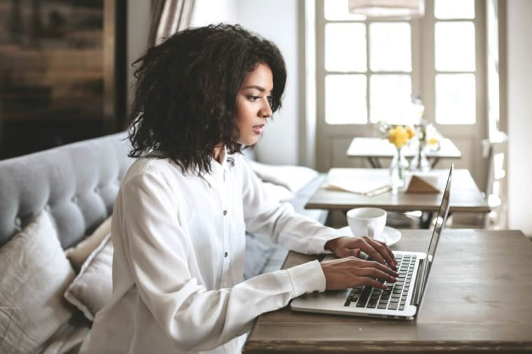 Young African American girl sitting in restaurant and typing on her laptop. Pretty girl working on computer at cafe. Portrait of lady with dark curly hair pensively looking in laptop