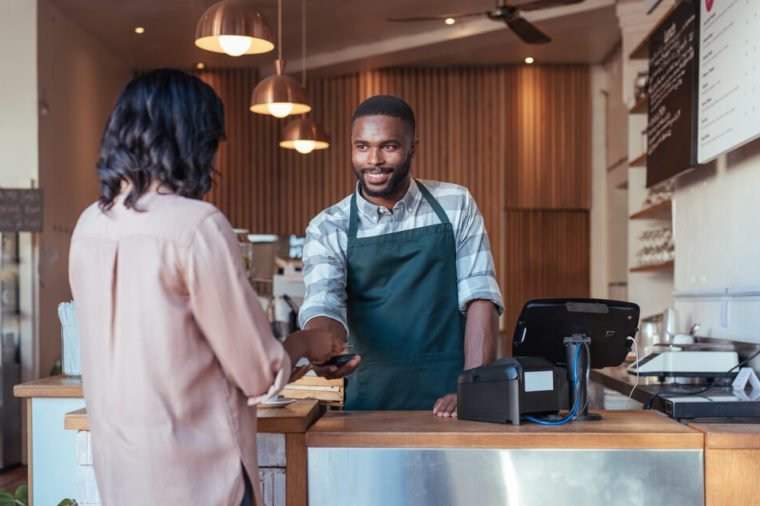 Smiling barista using nfs technology to help a customer pay for a purchase with their smartphone in a cafe
