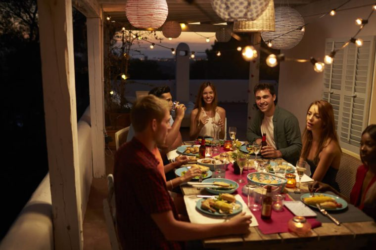 Friends talking at a dinner party on a patio, Ibiza, Spain