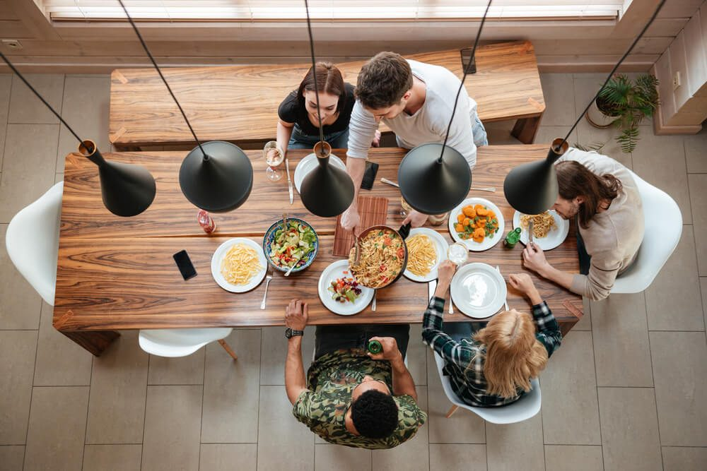 Top view of group of people having dinner together while sitting at the rustic wooden table at home