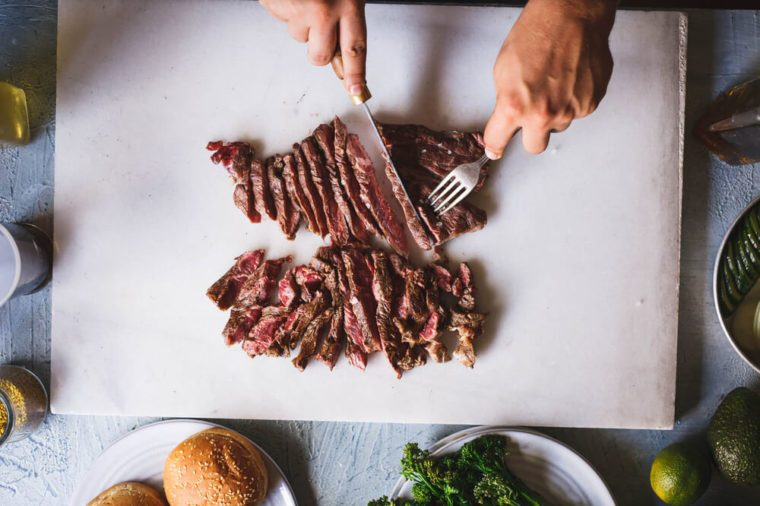 Person cutting beef grill steak in sliced over marble kitchen table overhead hot beef grilled steak