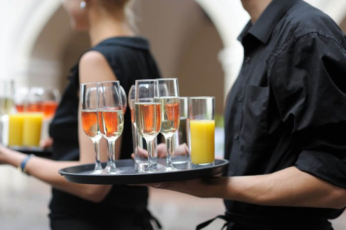 Waiter with dish of champagne, wine and juice glasses