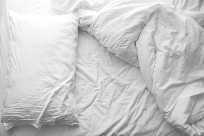 Messy bed. White pillow with blanket on bed unmade. Concept of relaxing after morning. With lighting window. Black and white theme.