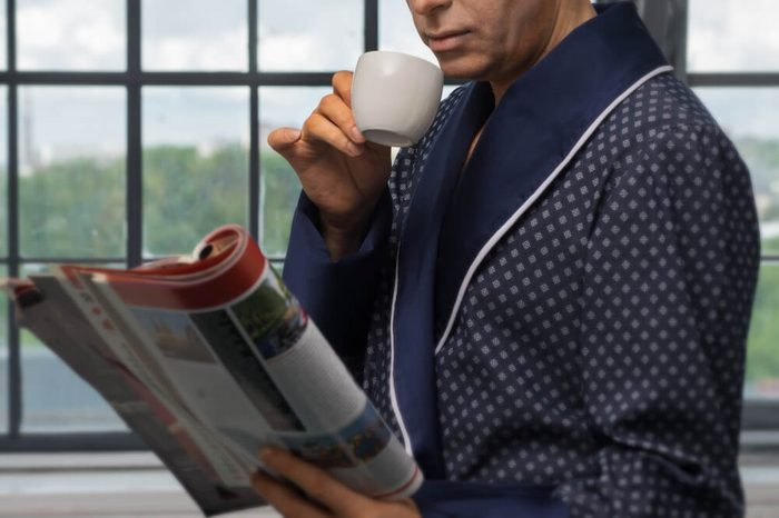 A man in a fashionable coat, sitting near the window, drinking coffee at breakfast and reading a magazine