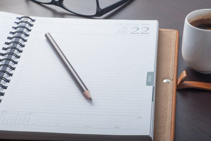 Close up of a working desk with a notebook, pencil, coffee cup and eyeglasses