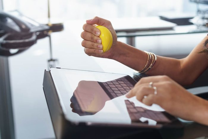 Office worker typing email on tablet computer. The woman feels stressed and nervous, holds an antistress yellow ball in her hand