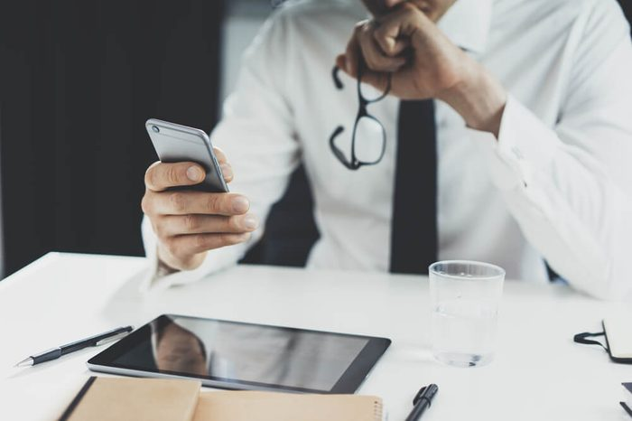 Close-up of businessman holding glasses and working on smartphone at his office, close-up of male hands using mobile phone, digital tablet and office tools on the desk