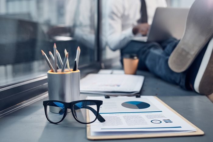 Necessary things. Close-up of document folder, trendy glasses and box of pencils are on windowsill with young businessman is sitting in background and typing on laptop