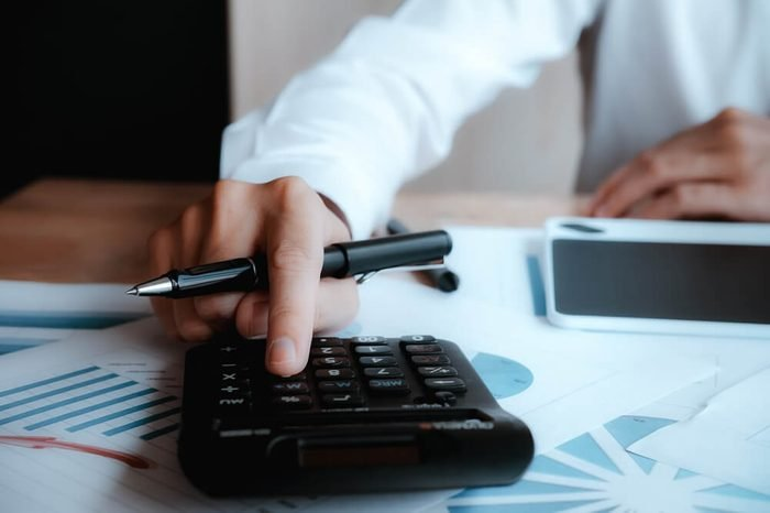 Close up asian Business man using a calculator to calculate the numbers.Business finances and accounting concept