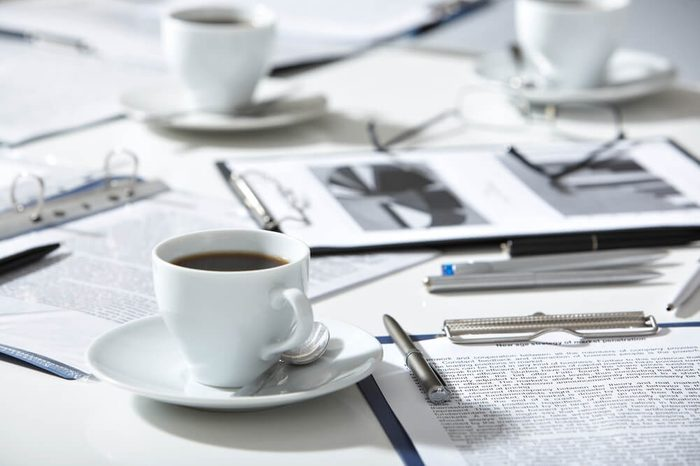 Close-up of documents, pen, cup of coffee on the table