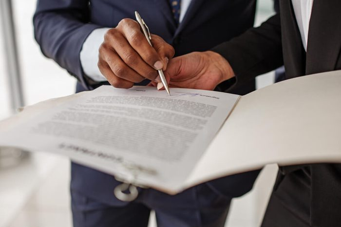 Sign it here. Woman is standing in office and holding folder with contract while man in suit is signing it. Close up of hand with pan. Selective focus