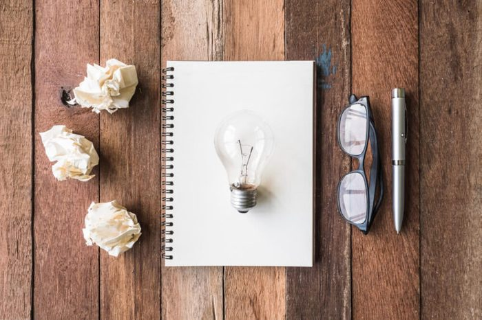 Top view of notebook with crumpled paper balls, pen, glasses and light bulb on wooden table background.