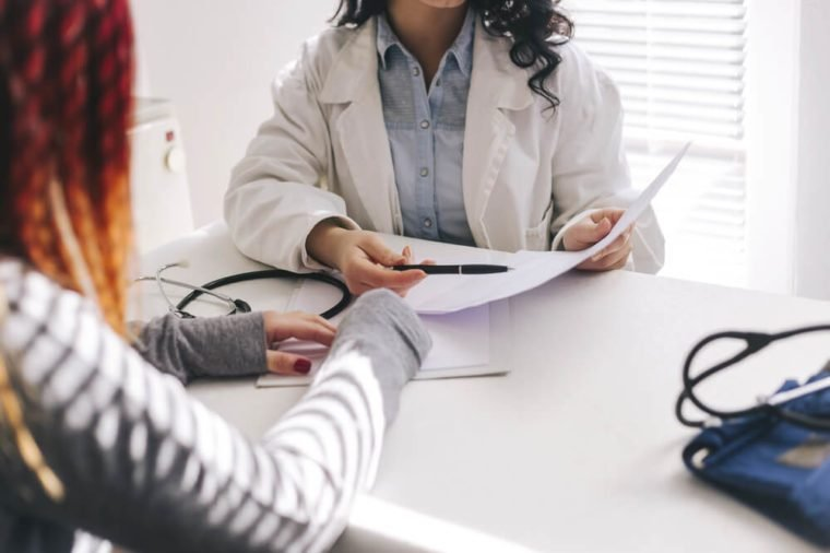 Doctor and patient are discussing about diagnosis. Medical doctor on white background holding a stethoscope, looking at medical form and taking notes.