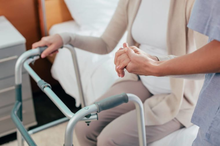 cropped shot of senior patient with walker and nurse holding hands