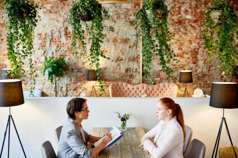 Profile view of female HR manager conducting interview with young red-haired applicant for position while sitting at fashionable restaurant with creative design