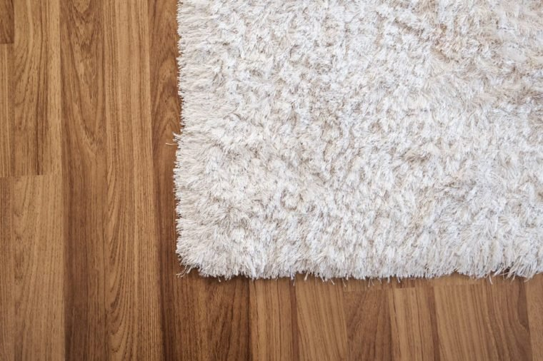 Close-up white carpet on laminate wood floor in living room, interior decoration