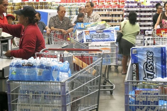 Shoppers stock up on cases of bottled water and other supplies in preparation for a hurricane and tropical storm heading toward Hawaii at the Iwilei Costco in Honolulu on . Two big storms so close together is rare in the eastern Pacific, and Hurricane Iselle could make landfall by Friday and Tropical Storm Julio could hit two or three days later, weather officials said
