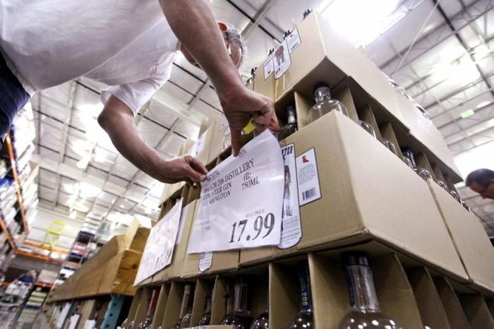 Store wine steward Robert Shelden places price signs on boxes of gin at a Costco warehouse store, in Seattle. Private retailers begin selling spirits for the first time under a voter-approved initiative kicking the state out of the liquor business. The initiative allows stores larger than 10,000 square feet and some smaller stores to sell hard alcohol