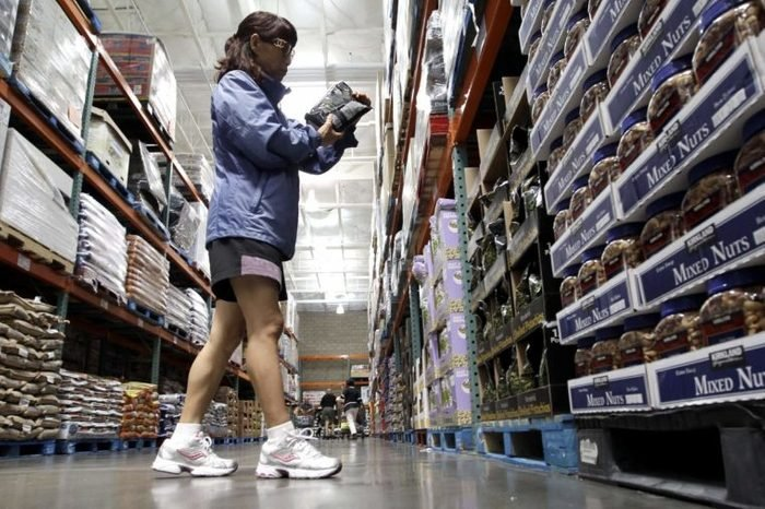 This photo, shows a shopper reading a product label at Costco Wholesale in Mountain View, Calif. Wholesale businesses boosted their stockpiles for a 19th consecutive month in July, but their sales were flat. Faltering demand could force businesses to cut back on orders when the economy is at risk of another recession