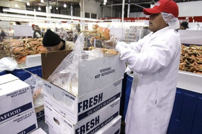 A Costco worker displays cooked Dungeness crab for sale at Costco Wholesale in Mountain View, Calif. . The Dungeness crab season opened this week