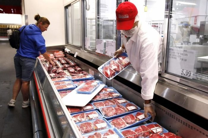 A Costco butcher puts out beef at Costco in Mountain View, Calif. Wholesale prices rose last month for the second straight month as the cost of energy climbed enough to offset an unexpected drop in food prices