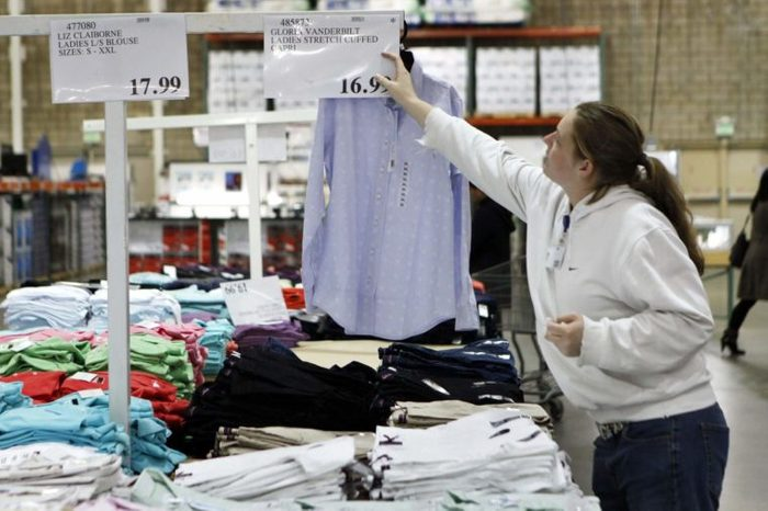 A Costco worker changes the price sign at Costco in Mountain View, Calif. Businesses trimmed inventories at the wholesale level again in January even though sales rose for a 10th consecutive month. The dip in inventories underscored that businesses remain cautious about restocking their depleted shelves