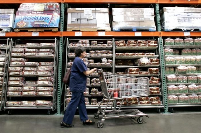 A shopper walks past shelves of bread at a Seattle Costco store . Costco Wholesale Corp. reported a 32 percent jump in its fiscal third-quarter profit Thursday, topping Wall Street expectations, as cash-squeezed customers flocked to its warehouse clubs in search of bargains on food and toiletries
