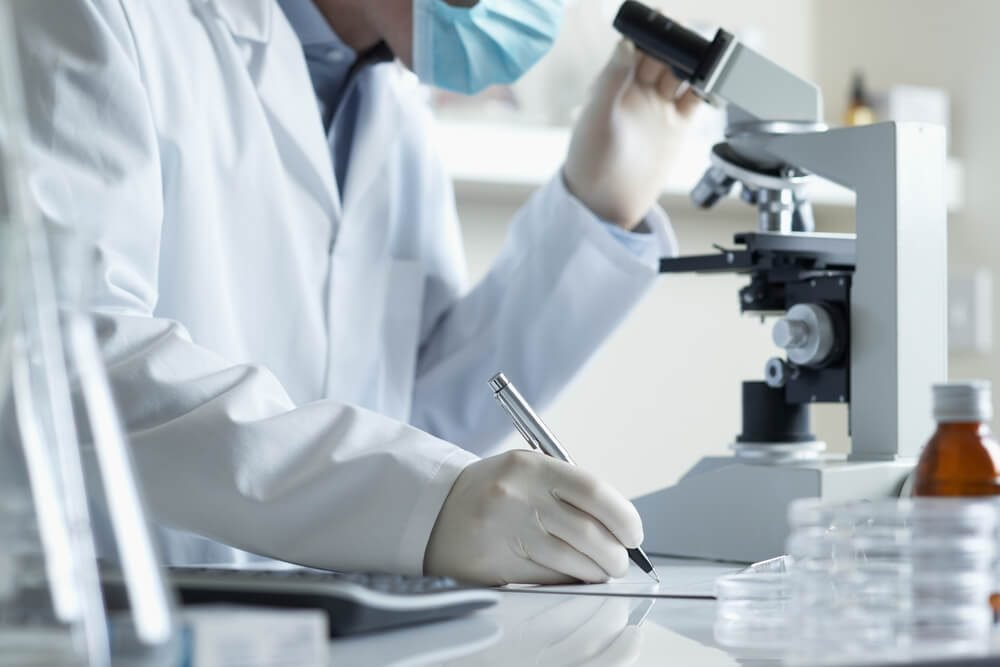 Scientist conducting research taking notes whilst looking through microscope selective focus