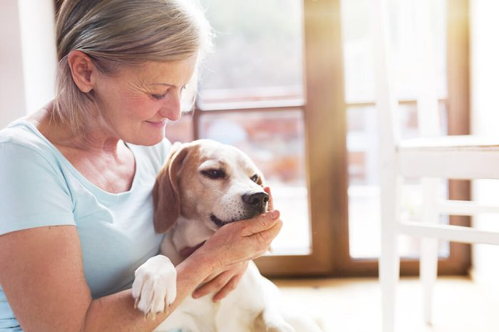 Senior woman with her dog inside of her house.
