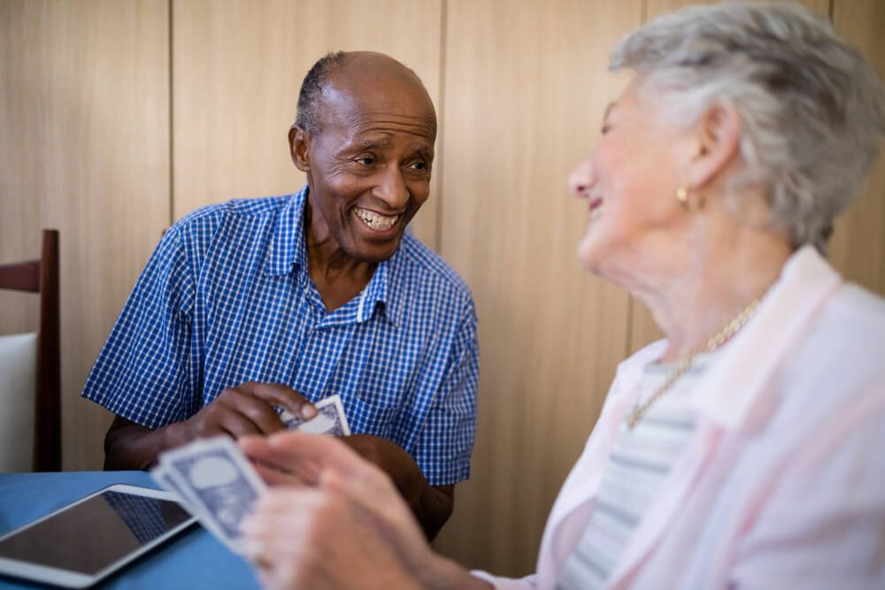Smiling senior male and female friends playing cards at table in nursing home