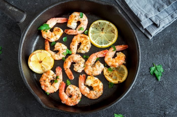 Roasted shrimps with lemon, garlic and herbs. Seafood, shelfish. Shrimps Prawns grilled with spices, garlic and lemon on black stone background, copy space. Shrimps prawns on cast iron pan.