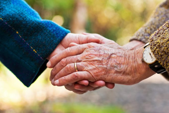 Elderly couple holding hands outdoors.