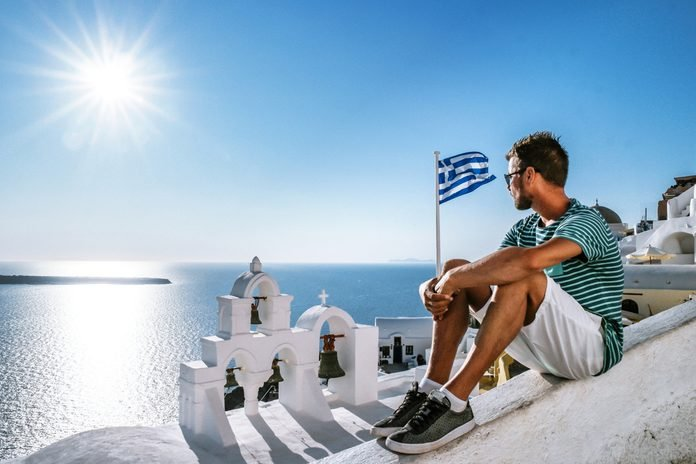 Santorini Oia Greece Young man looking out over the village on a bright summer day at the white washed bouldings of Santorini