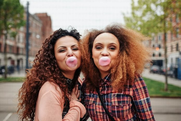Happy young women blowing bubble gum. Best friends chewing bubble gum, outdoors.