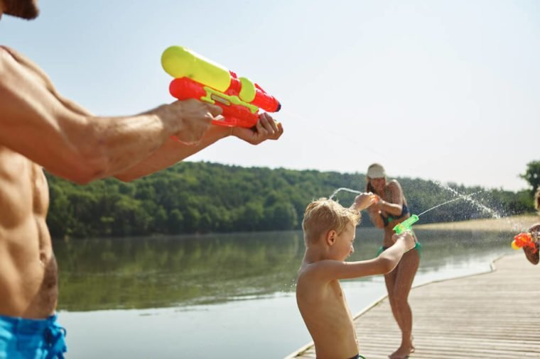Family at a lake spraying water to each other with a squirt gun and having fun in summer